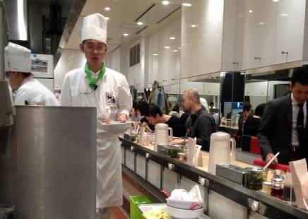 Ein Koch serviert heißen Ramen, ein typisches japanisches Essen