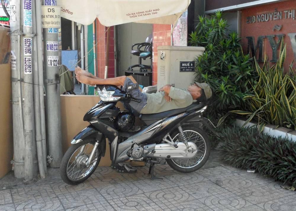 Vietnamese schläft auf seinem Roller in Ho Chi Minh Stadt