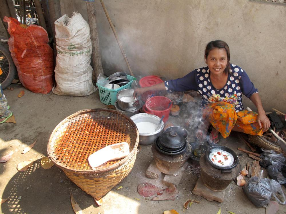 Frau in Myanmar bereitet Reispfannkuchen zu